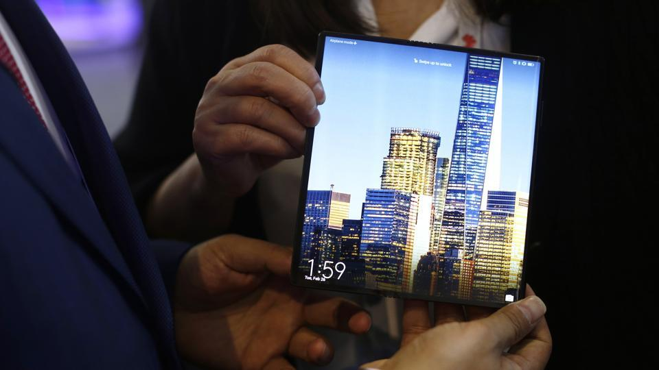 FILE - In this Tuesday, Feb. 26, 2019 file photo, a man holds the new Huawei Mate X foldable 5G smartphone during the Mobile World Congress wireless show, in Barcelona, Spain.