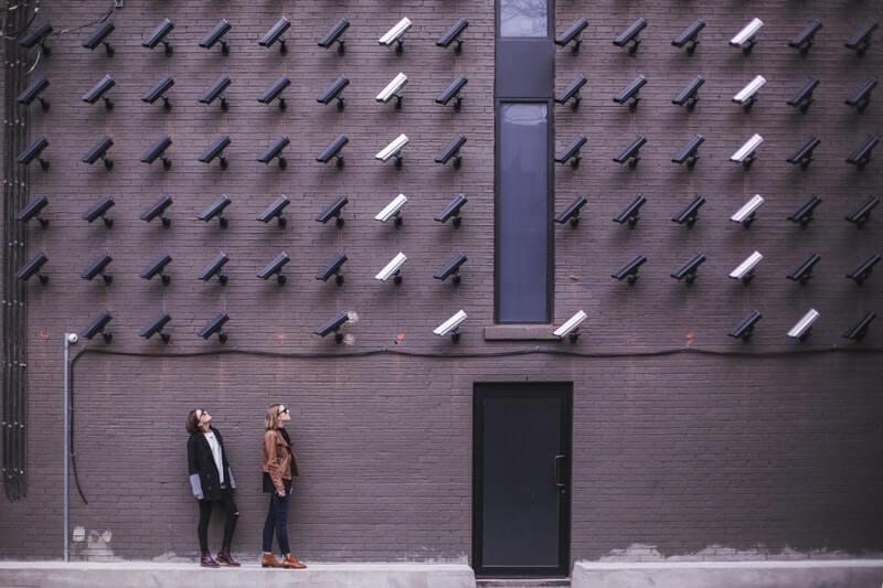 Dos personas mirando cámaras de seguridad blancas y negras