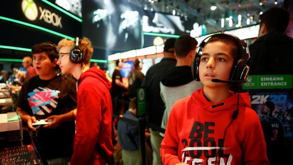 Boys play video games at the booth of Microsoft