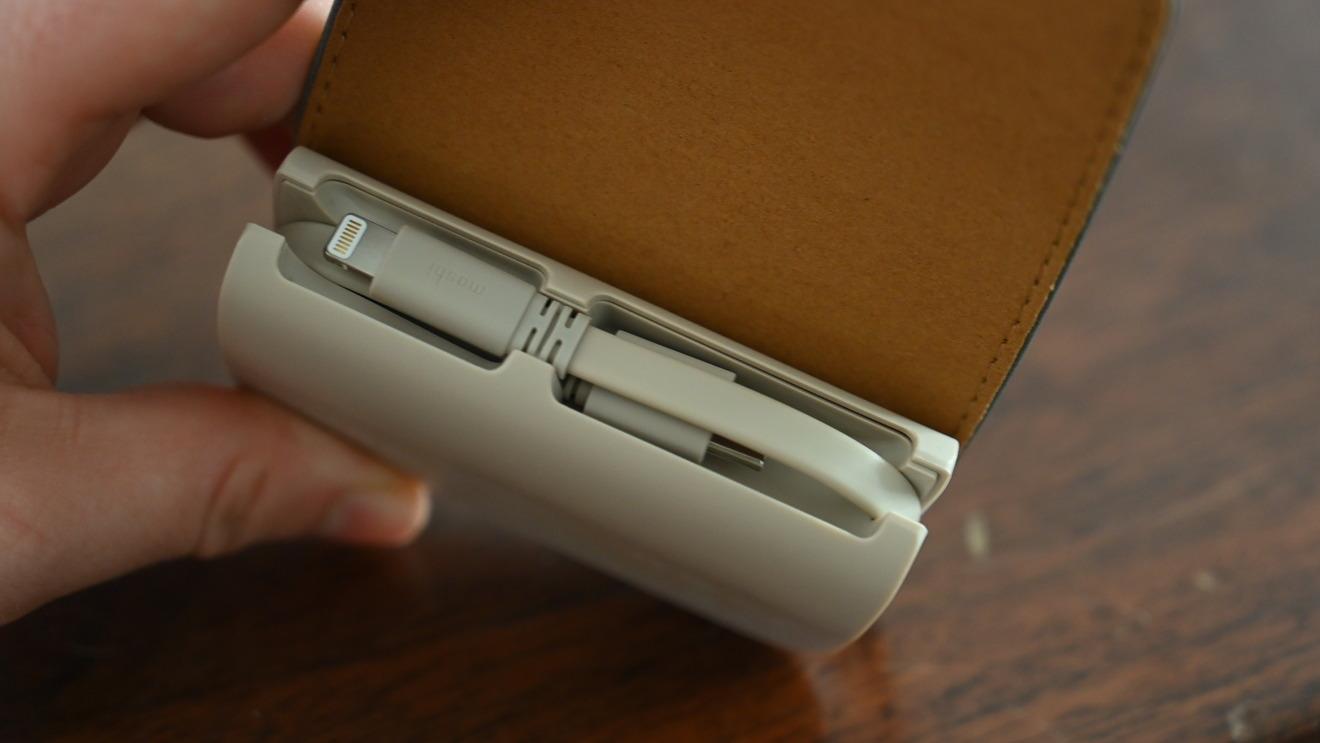 Un cable USB-C y Lightning se coloca detrás de una cubierta de cuero vegano que se asegura mediante imanes